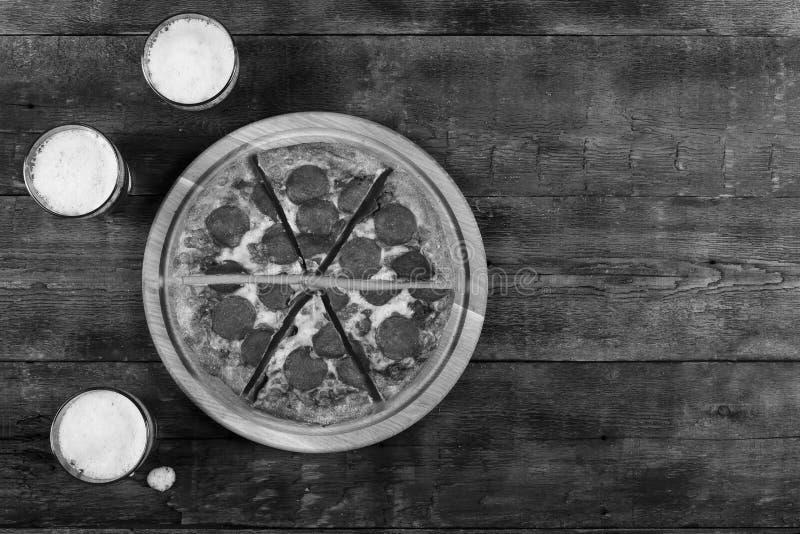 Píldoras de la pizza y de la cerveza de salchichones en una tabla de madera en el pub, visión superior, estilo rústico Copie el e fotos de archivo libres de regalías