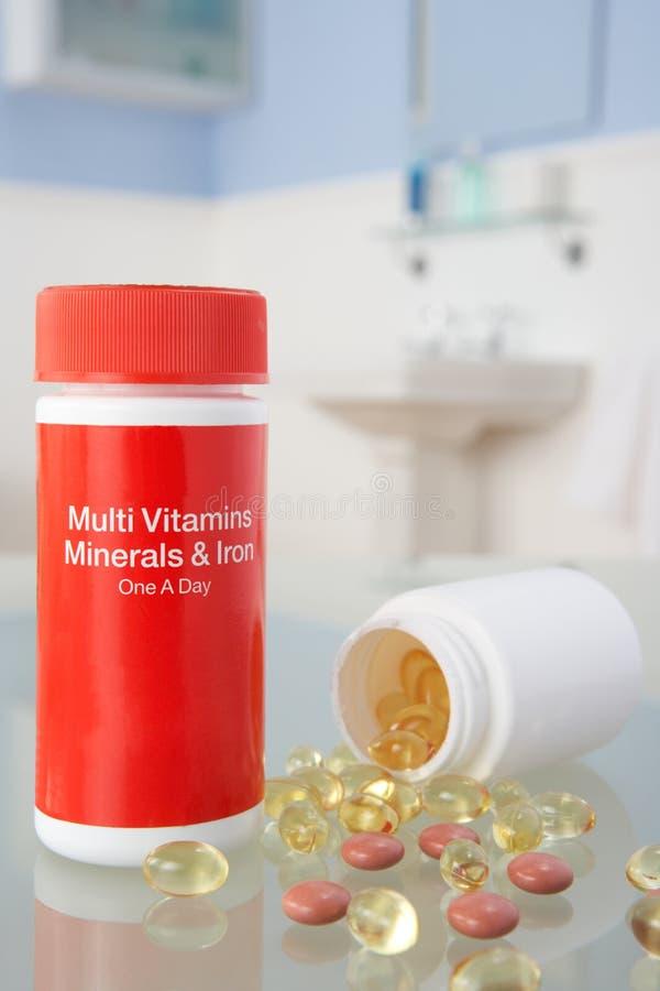 Píldoras de la vitamina en estante del cuarto de baño imagenes de archivo
