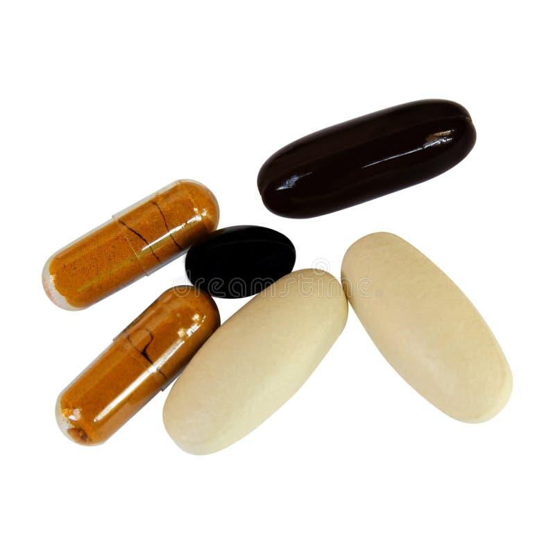 Píldoras de los suplementos de la vitamina C y de la medicina herbaria en blanco fotografía de archivo