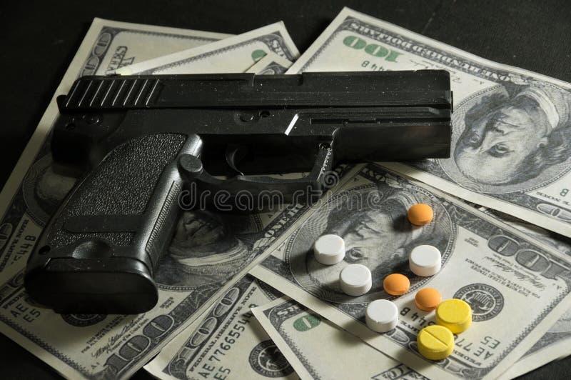 Píldoras del arma y de la droga en billetes de dólar fotos de archivo