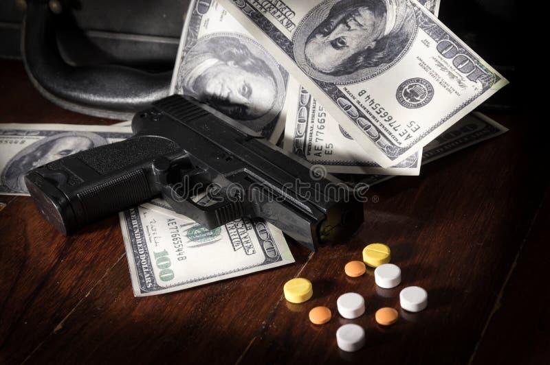 Píldoras del arma y de la droga en billetes de dólar imagenes de archivo