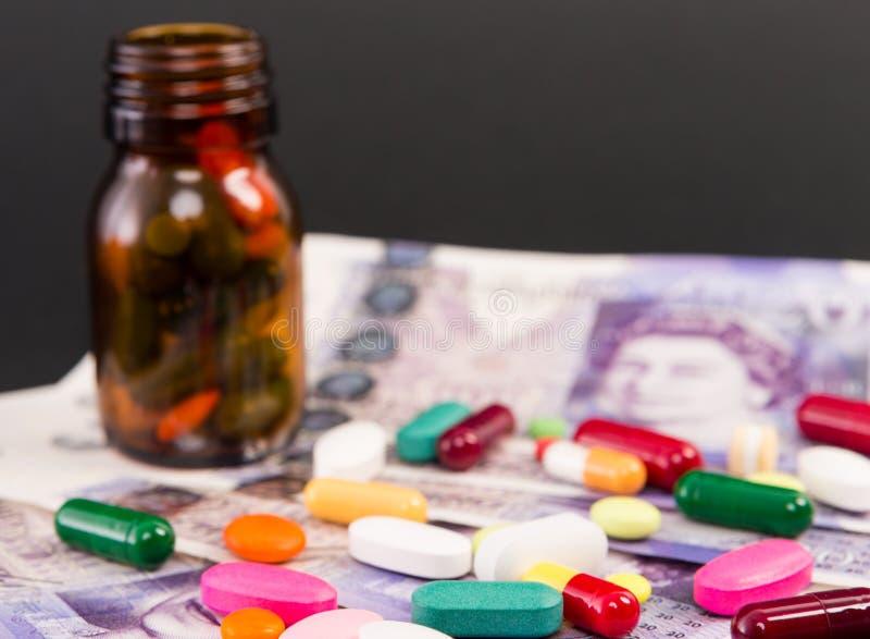 Píldoras derramadas en billetes de banco de las libras británicas imágenes de archivo libres de regalías