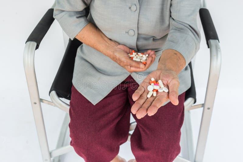 píldoras a disposición, mujer mayor que se sienta en silla y que sostiene la píldora i fotografía de archivo libre de regalías