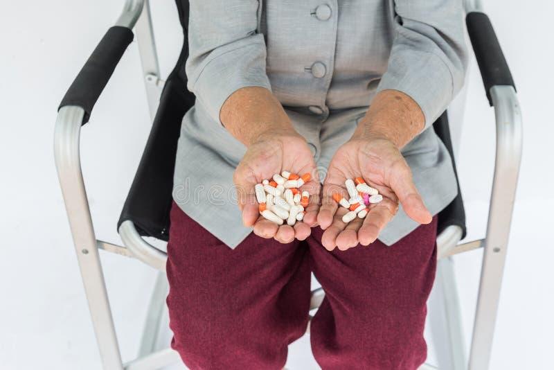 píldoras a disposición, mujer mayor que se sienta en silla y que sostiene la píldora i imagen de archivo