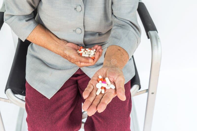 píldoras a disposición, mujer mayor que se sienta en silla y que sostiene la píldora i fotografía de archivo