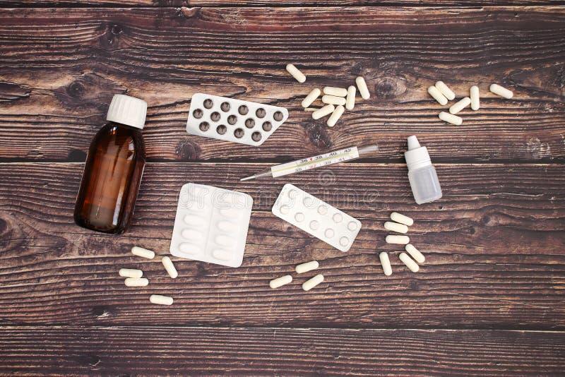 Píldoras e instrumentos médicos en la tabla de madera imágenes de archivo libres de regalías