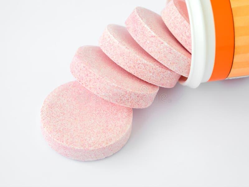 Píldoras efervescentes solubles de la vitamina derramadas fuera de una botella plástica en un fondo blanco Vitaminas y suplemento fotografía de archivo libre de regalías