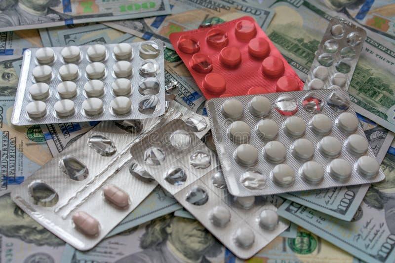 Píldoras en el dinero de 100 dólares Costos de la medicina Altos costes del concepto costoso de la medicación foto de archivo
