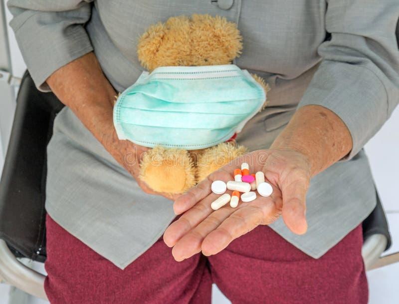 píldoras en mano mayor y sostener de la mujer el oso de peluche con la máscara en f imagenes de archivo