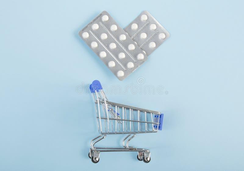 Píldoras en un paquete de ampolla en la forma de un corazón con el carro de la compra en fondo azul fotografía de archivo