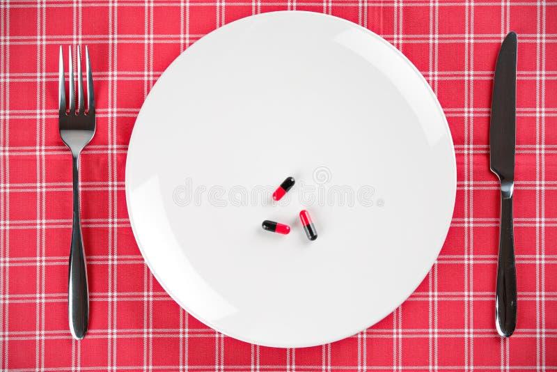 Píldoras en una placa con la fork y el cuchillo fotografía de archivo