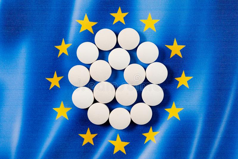 Píldoras farmacéuticas redondas blancas en fondo de la bandera de unión europea imagen de archivo