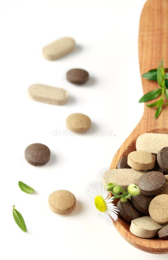 Píldoras herbarias en una cuchara de madera para la medicina alternativa y el ayurveda para la salud en un fondo blanco imagen de archivo libre de regalías