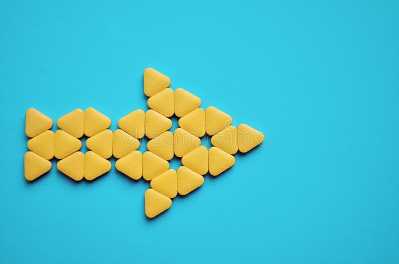 Píldoras inusuales triangulares amarillas apiladas en la forma de la flecha a la derecha, mentira en fondo azul con el copyspace, fotos de archivo libres de regalías