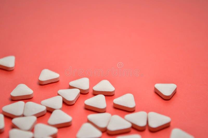 Píldoras inusuales triangulares blancas dispersadas en un fondo rosado con el espacio para el texto imagen de archivo libre de regalías