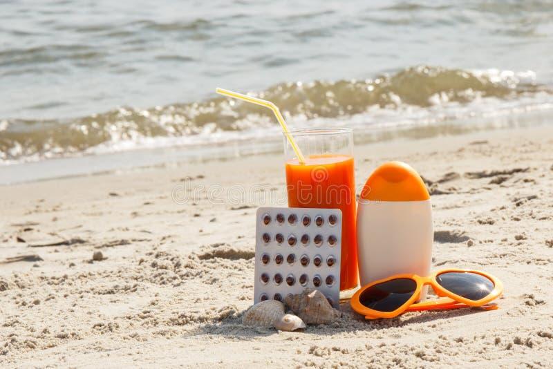 Píldoras, jugo de zanahoria y accesorios médicos para tomar el sol en la playa fotos de archivo