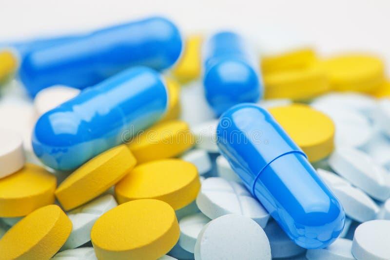 Píldoras médicas azules en un fondo de diversas tabletas del color imágenes de archivo libres de regalías