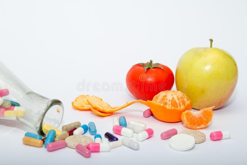 Píldoras médicas coloridas en un envase de cristal en un fondo blanco imagen de archivo