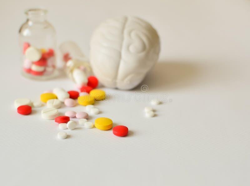 Píldoras multicoloras y un modelo del cerebro humano en la parte posterior del cautiverio El concepto de tratamiento de las enfer foto de archivo libre de regalías