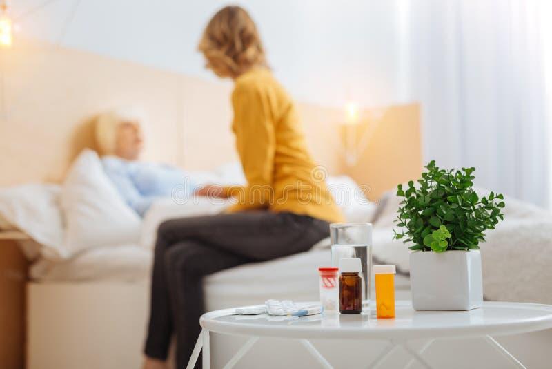 Píldoras necesarias que están en la tabla mientras que una mujer envejecida que está en su cama foto de archivo libre de regalías