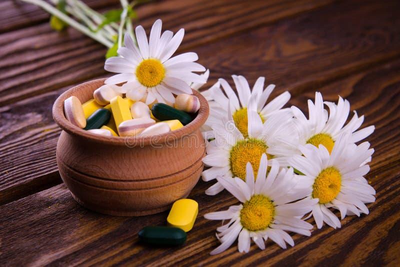 Píldoras orgánicas con la manzanilla foto de archivo