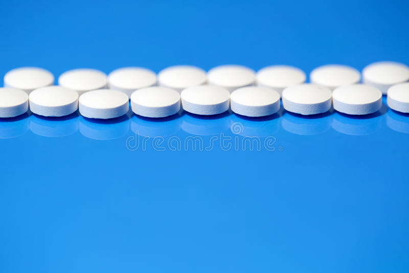 Píldoras Píldoras médicas blancas en fondo azul imagen de archivo libre de regalías