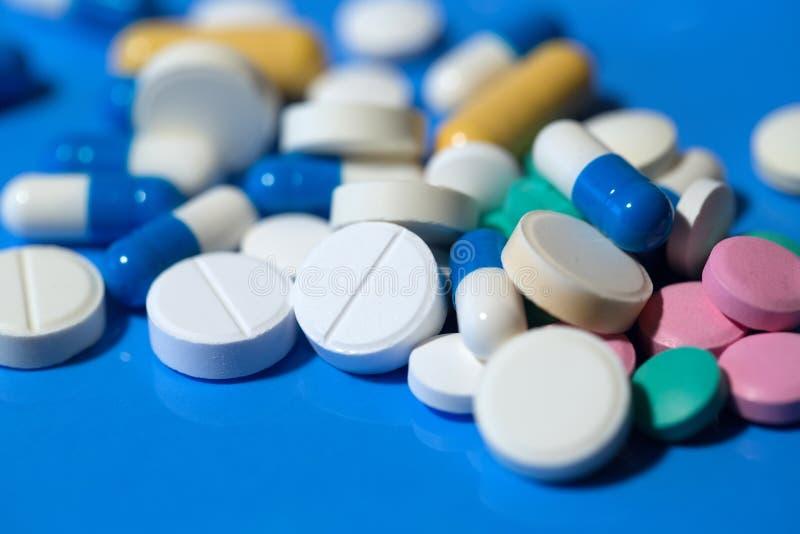 Píldoras Píldoras médicas blancas en fondo azul foto de archivo libre de regalías