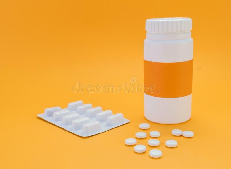 Píldoras que desbordan una botella abierta en fondo anaranjado foto de archivo libre de regalías