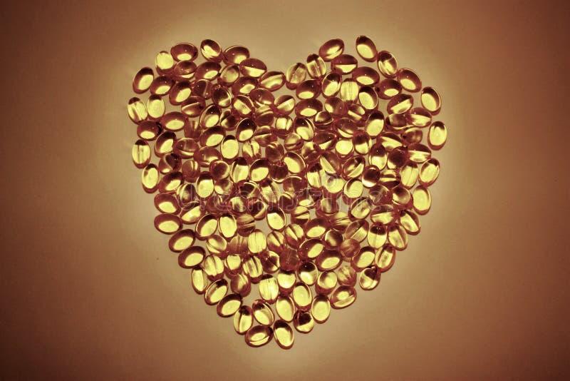 Píldoras que mienten en la forma de un corazón en el fondo blanco, cápsulas amarillas Omega 3 del gel imagenes de archivo