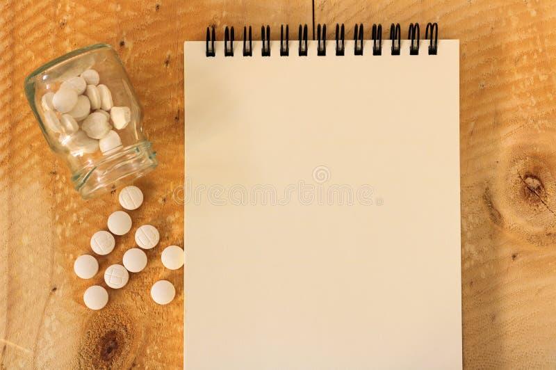 Píldoras que se derraman fuera de la botella de píldora en la tabla de madera imagenes de archivo