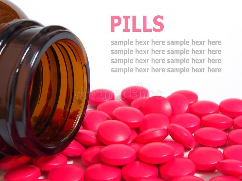 Píldoras que se derraman fuera de una botella de píldora aislada en blanco imagen de archivo libre de regalías