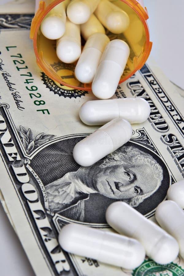Píldoras que se derraman sobre dólar fotos de archivo