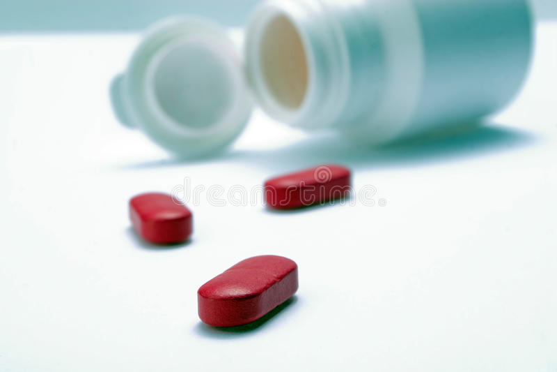 Píldoras rojas y una botella imagen de archivo