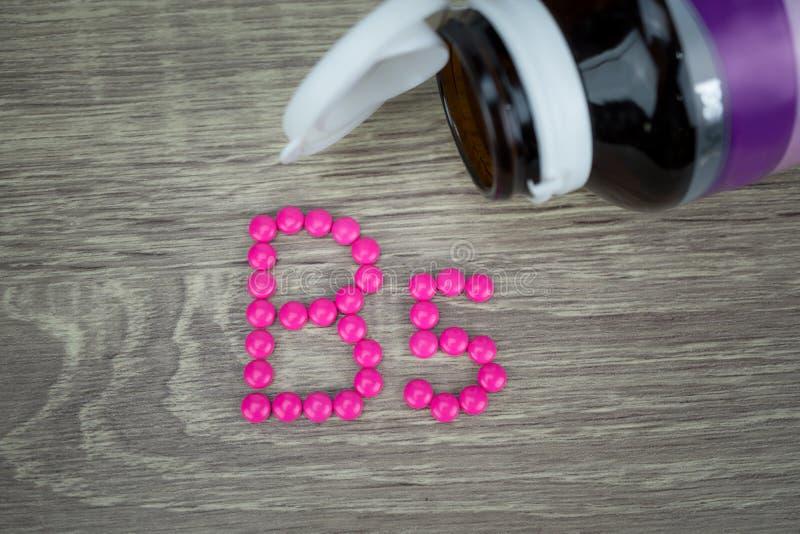 Píldoras rosadas que forman forma al alfabeto B5 en el fondo de madera foto de archivo