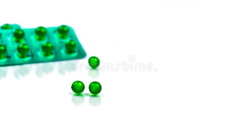 Píldoras suaves redondas verdes de la cápsula en el fondo borroso del paquete de ampolla con el espacio Medicina de Ayurvedic par fotografía de archivo