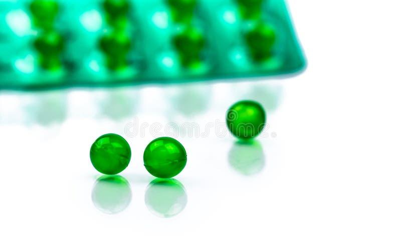 Píldoras suaves redondas verdes de la cápsula en el fondo borroso del paquete de ampolla con el espacio Medicina de Ayurvedic par fotos de archivo libres de regalías