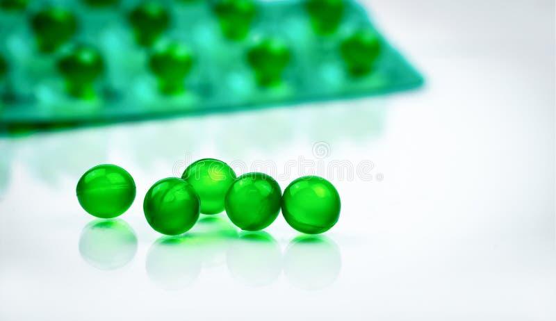 Píldoras suaves redondas verdes de la cápsula en el fondo borroso del paquete de ampolla con el espacio Medicina de Ayurvedic par foto de archivo libre de regalías