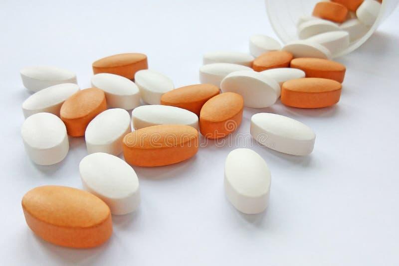 Píldoras, tabletas y cápsulas farmacéuticas coloridas clasificadas de la medicina con la botella en el fondo blanco foto de archivo libre de regalías