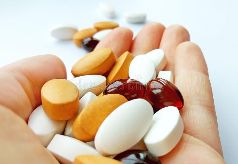 Píldoras, tabletas y cápsulas farmacéuticas coloridas de la medicina a disposición en el fondo blanco fotos de archivo libres de regalías
