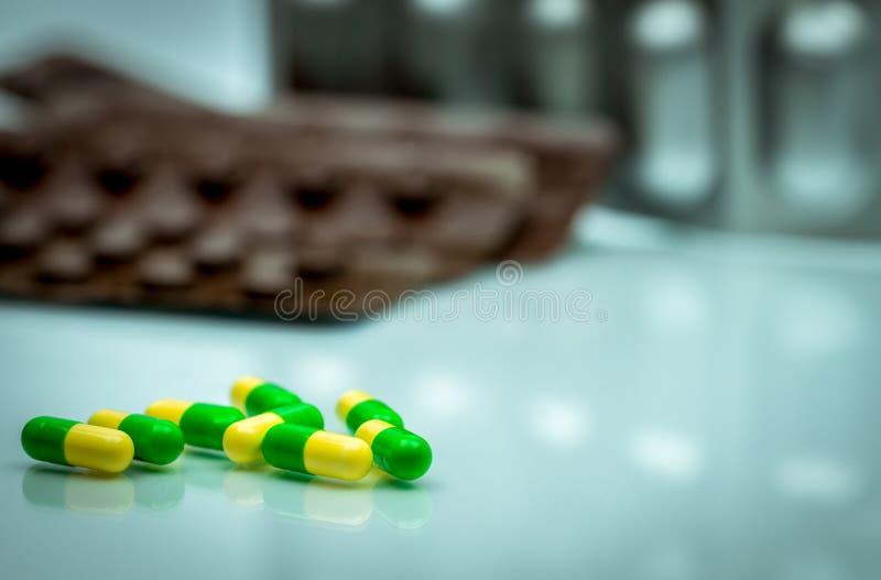 Píldoras verdes, amarillas de la cápsula del tramadol en el CCB borroso del paquete de ampolla imagenes de archivo
