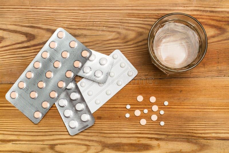 Píldoras y ampollas médicas de la píldora con un vaso de agua imagen de archivo libre de regalías