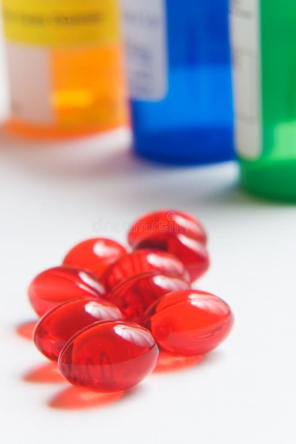 Píldoras y botellas rojas de la prescripción fotos de archivo libres de regalías