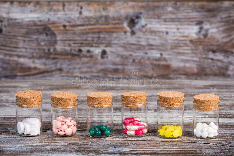 Píldoras y cápsulas en los envases de cristal imagen de archivo