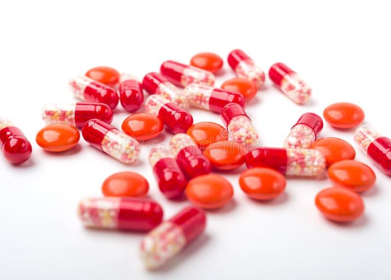 Píldoras y cápsulas rojas derramadas de la medicina foto de archivo