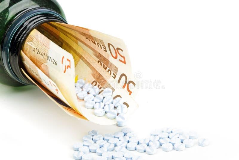 Píldoras y dinero euro fotos de archivo