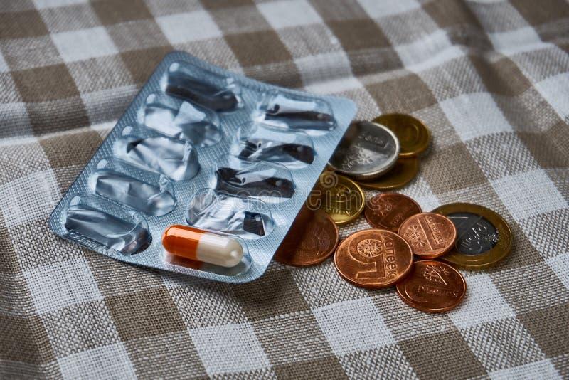Píldoras y monedas, medicamento costoso, pobreza de la conclusión imagenes de archivo