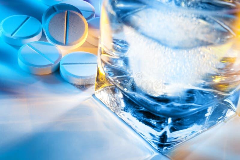 Píldoras y vidrio de agua imagen de archivo