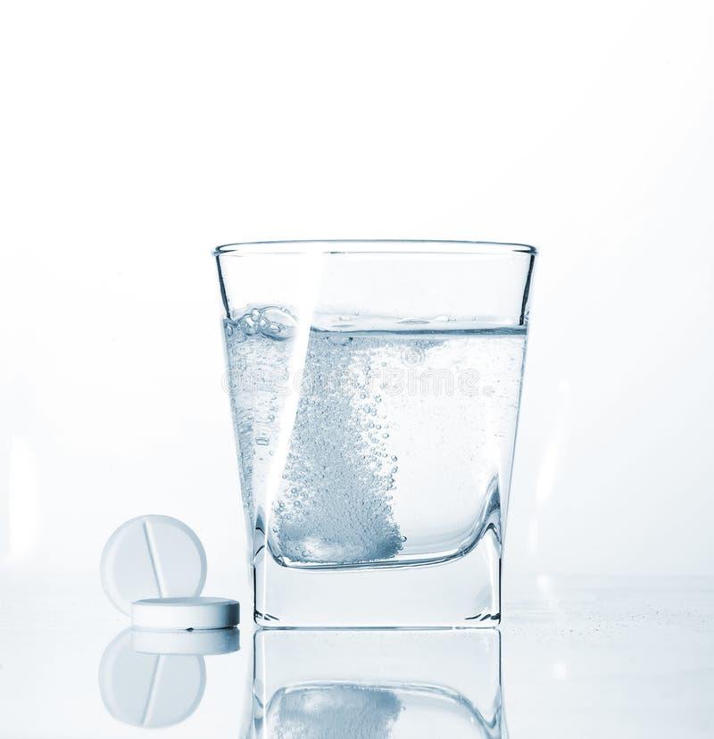 Píldoras y vidrio de agua chispeante fotos de archivo