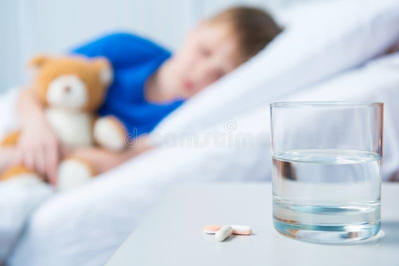 Píldoras y vidrio de agua en la tabla y el muchacho que mienten en cama de hospital con el oso de peluche foto de archivo libre de regalías
