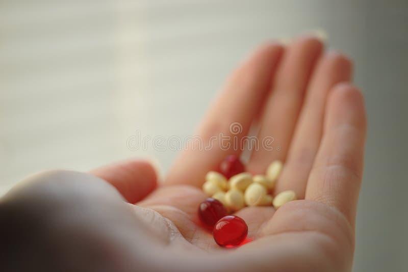 Pílulas médicas na mão jovem Vitaminas na palma humana imagem de stock